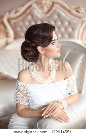 Retro woman portrait. Elegant brunette lady with fashion pearls jewelry set, french manicure nails, wavy hairstyle and makeup. Gorgeous model posing on luxury armchair in modern interior.