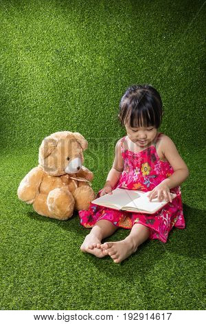 Asian Chinese Little Girl Reading Book With Teddy Bear