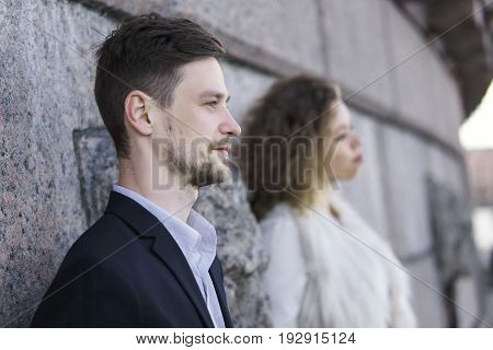 Couple posing against the background of a granite wall