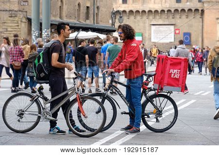 Bologna Italy 1 May 2017 - A Just Eat bike deliver courier speak with another cyclist in the Bologna's main square