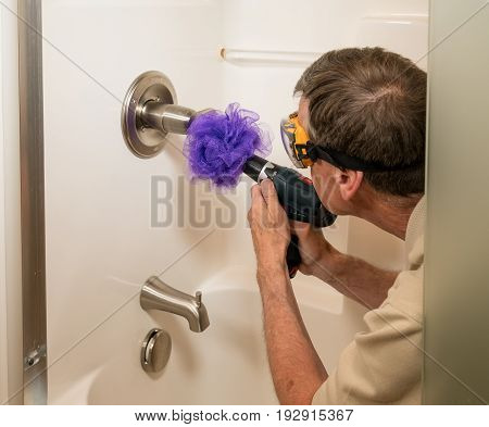 Senior working man cleaning a shower or bath with a power drill