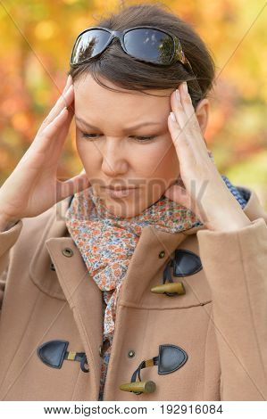 Young woman with headache in a park