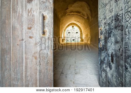 Entrance to abandoned fortress through big wooden gate Italy