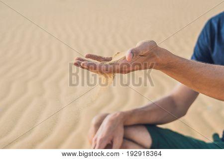 Desert, Sand Puffs Through The Fingers Of A Man's Hand