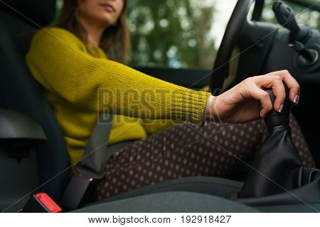Woman driving car and shifting gears on gearbox