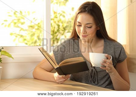 Relaxed woman reading a paper book and holding a cup of coffee sitting at a table at home with a warm light