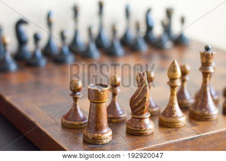 Vintage wooden chess pieces on an old chessboard.