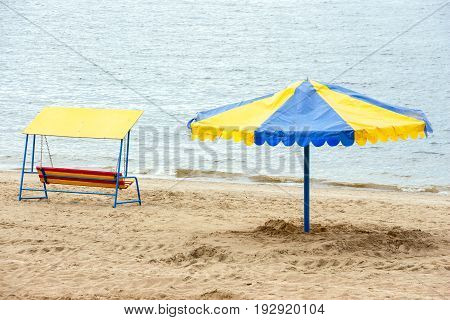 Umbrella and swing on a deserted river beach