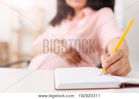 Put it down. Close up of pregnant woman holding a pencil and making notes in the notebook while sitting in the office