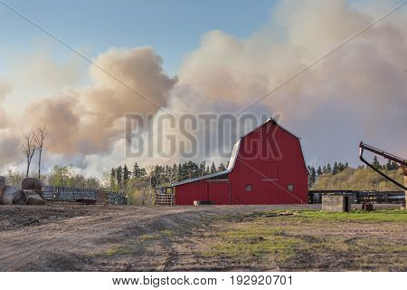 a red barn with a cloud of smoke behind it