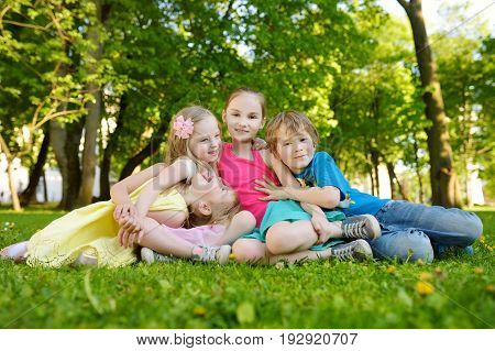 Four cute little children having fun together on the grass on a sunny summer day. Funny kids hanging together outdoors. Active family leisure.
