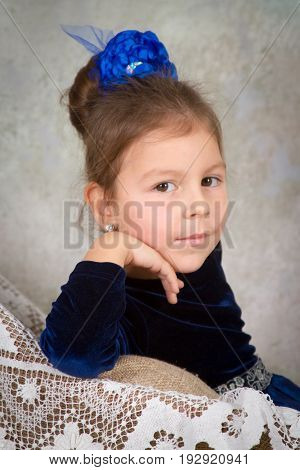 beautiful little girl princess in blue dress sitting on white chair and smiling