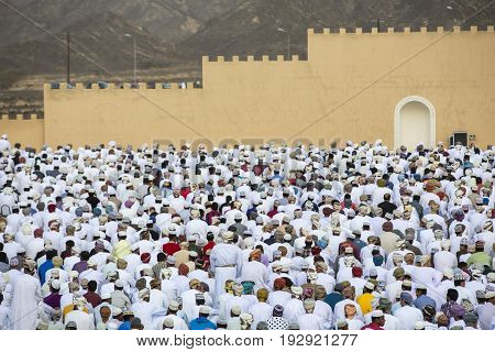 Nizwa Oman - June 26th 2017: Men praying at the start of Eid al Fitr the muslim holiday to celebrate the end of Holy Month of Ramadan