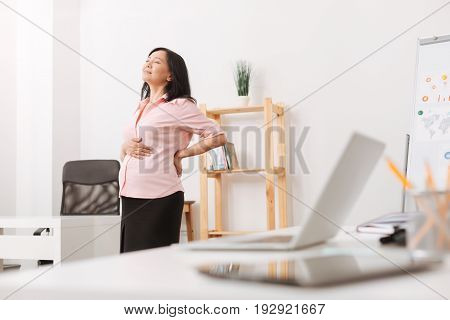 Treat a backache. Tired pregnant woman standing in the office and feeling a need of rest while having a backache