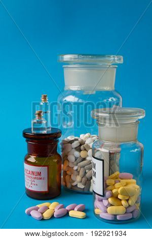 Colorful medical pills in a glass container and scattering on a blue background.