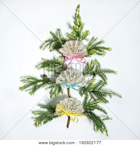 flat lay small christmas tree made from fir branches decorated with three fans, isolated on white background. new year and christmas concept of spanish, mexican or chinese fans.