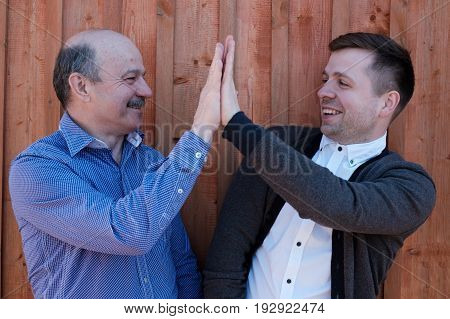 Father and son on wooden background. They celebrate success and claps in hands