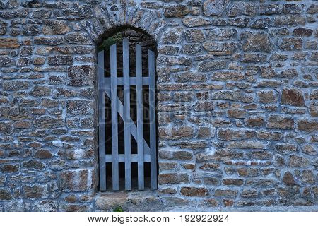 Wooden gate in a brick wall in france