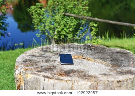 Smartphone on old stump. Nature and technology abstraction.