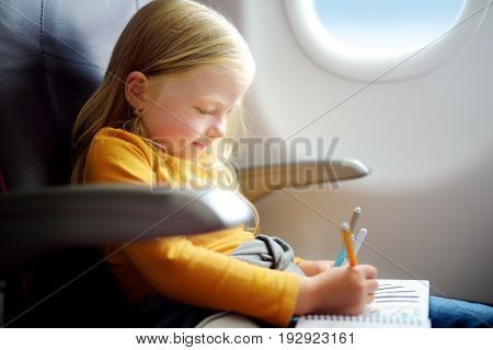Adorable Little Girl Traveling By An Airplane. Child Sitting By Aircraft Window And Drawing A Pictur