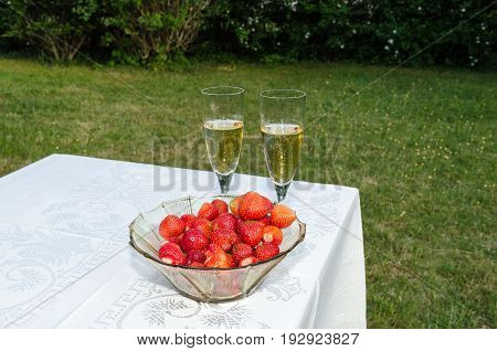 Bowl with fresh strawberries and two glasses sparkling wine on a table with a white cloth in the garden