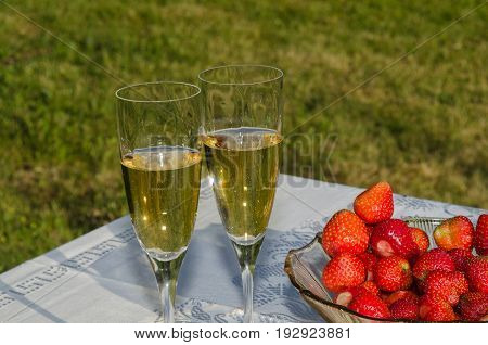 Table in a garden with two glasses sparkling wine and a bowl with fresh strawberries