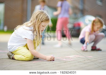 Cute Little Girl Drawing With Colorful Chalks On A Sidewalk. Summer Activity For Small Kids.