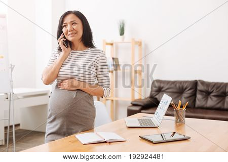 Call me soon. Delighted asian pregnant woman talking on phone and standing in the office while waiting for a maternity leave