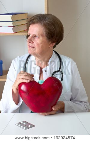 Female doctor with the stethoscope holding red heart.