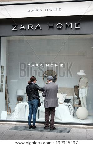 Bologna Italy 1 May 2017 - an old man and a woman look at the showcase of the Zara Home furnishing store in Bologna