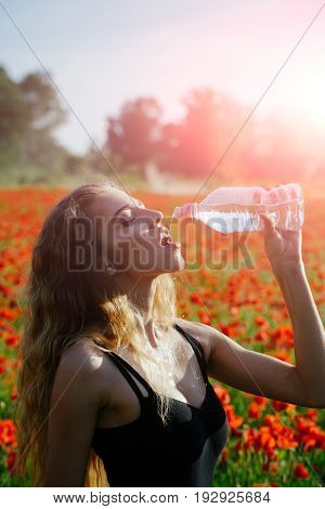 girl with long curly hair drink water from plastic bottle in flower field of red poppy summer drug and intoxication opium refreshment and relax sport and fitness healthcare and thirst youth