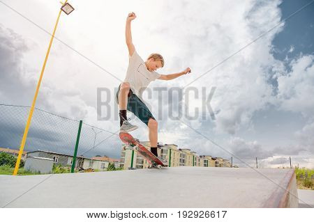 Boy skateboarder in a skate park doing an manual trick on a skateboard against a sky and thunderclouds