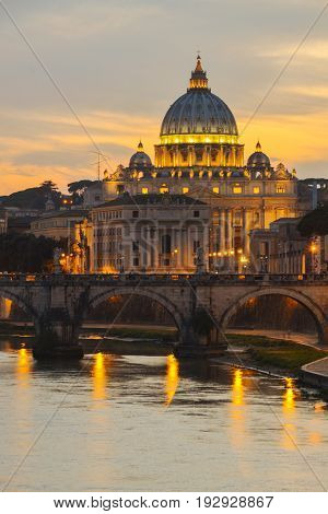 Monumental St. Peters Basilica over Tiber  at twilight in Rome, Italy
