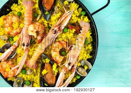 A closeup photo of a Spanish seafood paella in a typical paellera, with mussels, clams, and shrimps, with a place for text, shot from above on a teal texture