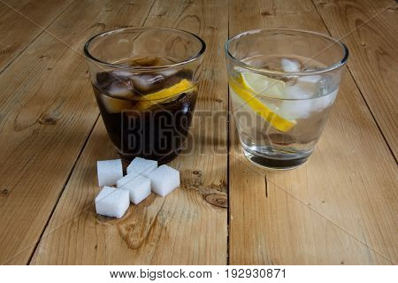 Cola and water on wood table with sugar cube