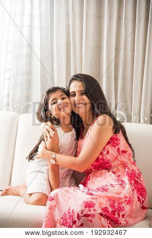 indian smart mother hugging her cute daughter, Portrait of happy Indian mother and daughter together while sitting on sofa
