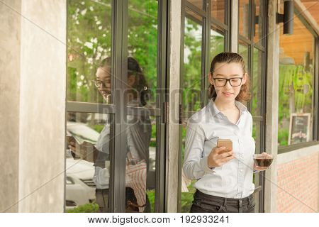 Half Thai half American hold iphone in right hand and glass of hot black coffee in left hand standing against glass door at coffee shop