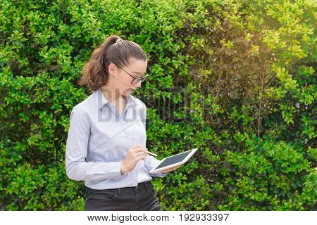 Portrait of Farmer agriculturist and cultivator or business woman in casual freelance dress work in green farmhand hold file sheet with pen and wear glasses.