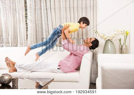 Happy Indian father playing with son while lying on sofa in living room at home. Asian Young man playing with small boy. child playfully punching his father or dad
