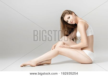 young beautiful brunette woman with perfect body in white underwear. sitting on floor. Smooth skin after depilation