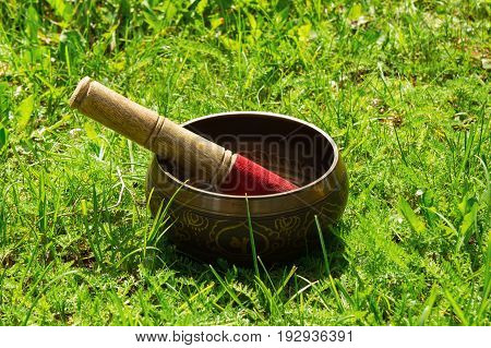 Tibetian Singing Bowl With Wooden Stick On The Grass.