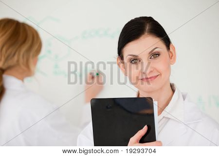 Scientist posing while another is writing a formula on a whiteboard