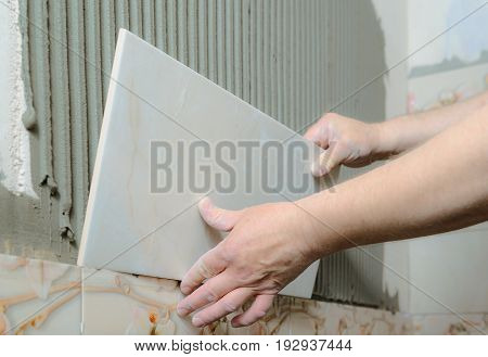 Tilers hands are installing a ceramic tile on a wall in a bathroom.