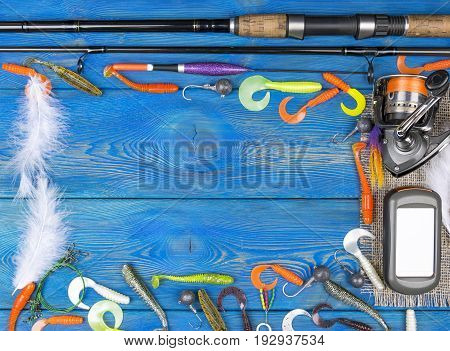 Fishing tackle - fishing spinning fishing line hooks navigator and reel on blue wooden background