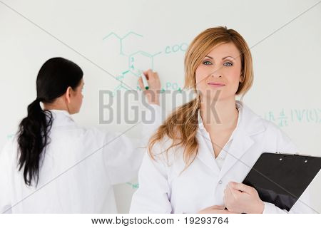 Woman looking at the camera while another is writing a formula