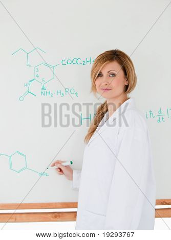 Scientist posing while writing on a whiteboard in a lab