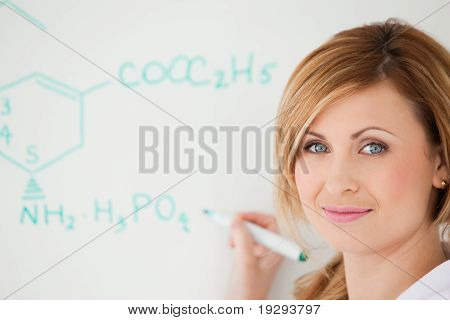 Blonde scientist posing while writing a formula