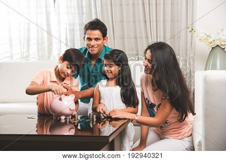 Happy young Indian couple teaching importance of saving to kids at home with piggy bank