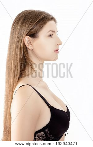 Profile portrait of a young  slender woman in black lingerie isolated on the white background