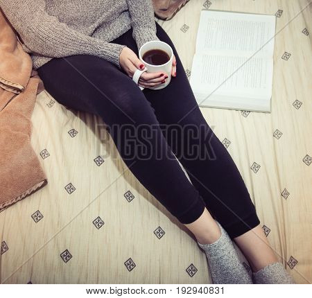 Relaxed woman in the morning.  Woman reading a book and drinking coffee in bed